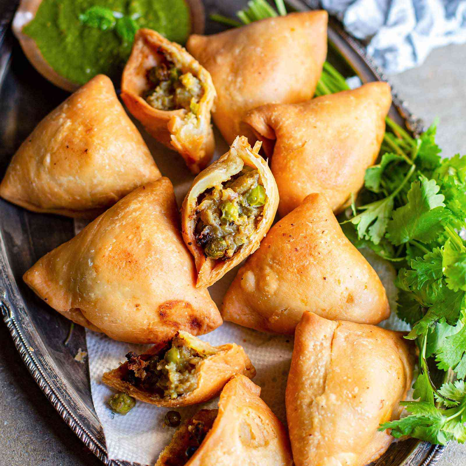 Golden Vegetarian Samosas on a bed of herbs with one samosa broken open to show the potato and pea filling.