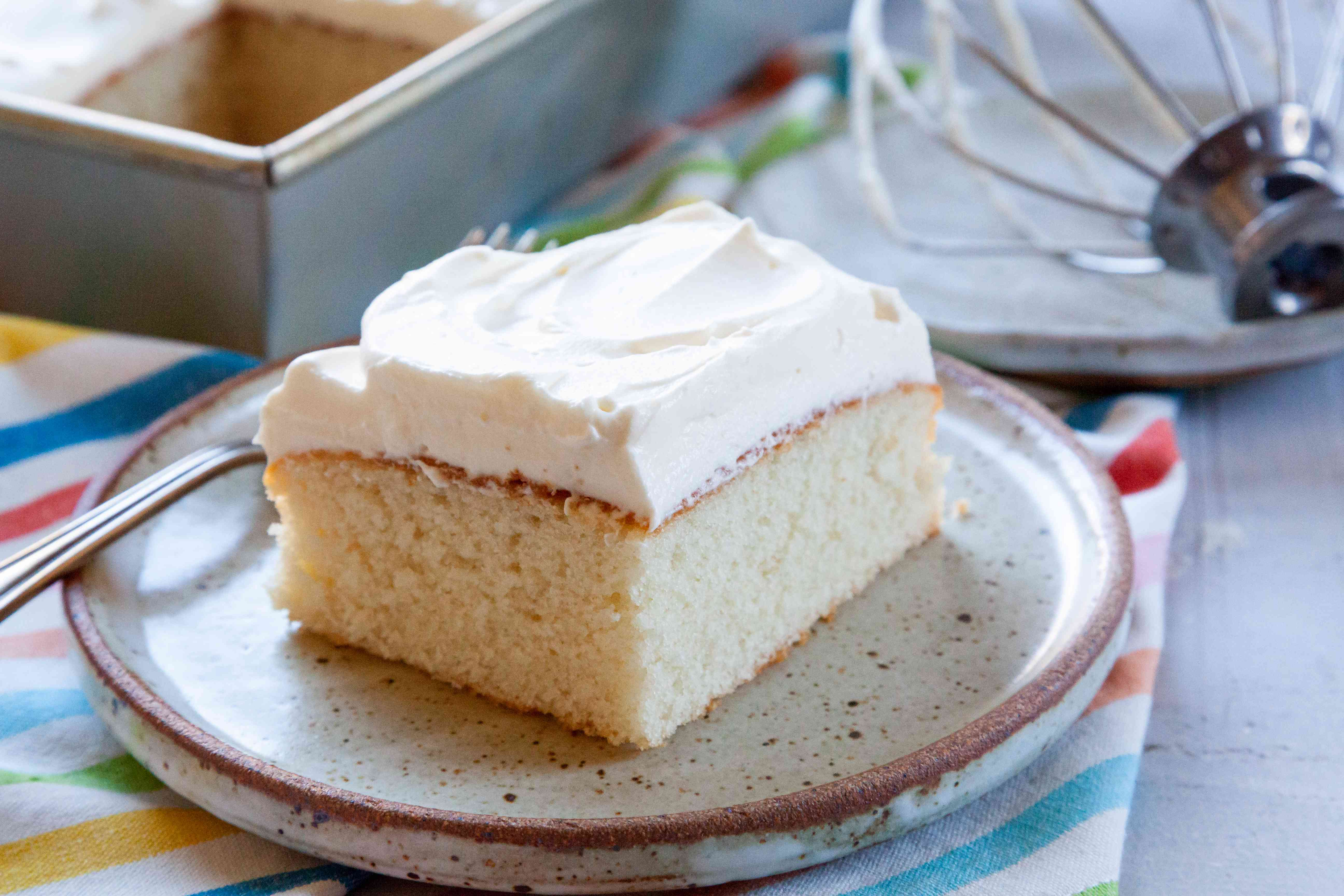 Easy white cake topped with frosting and on a plate.