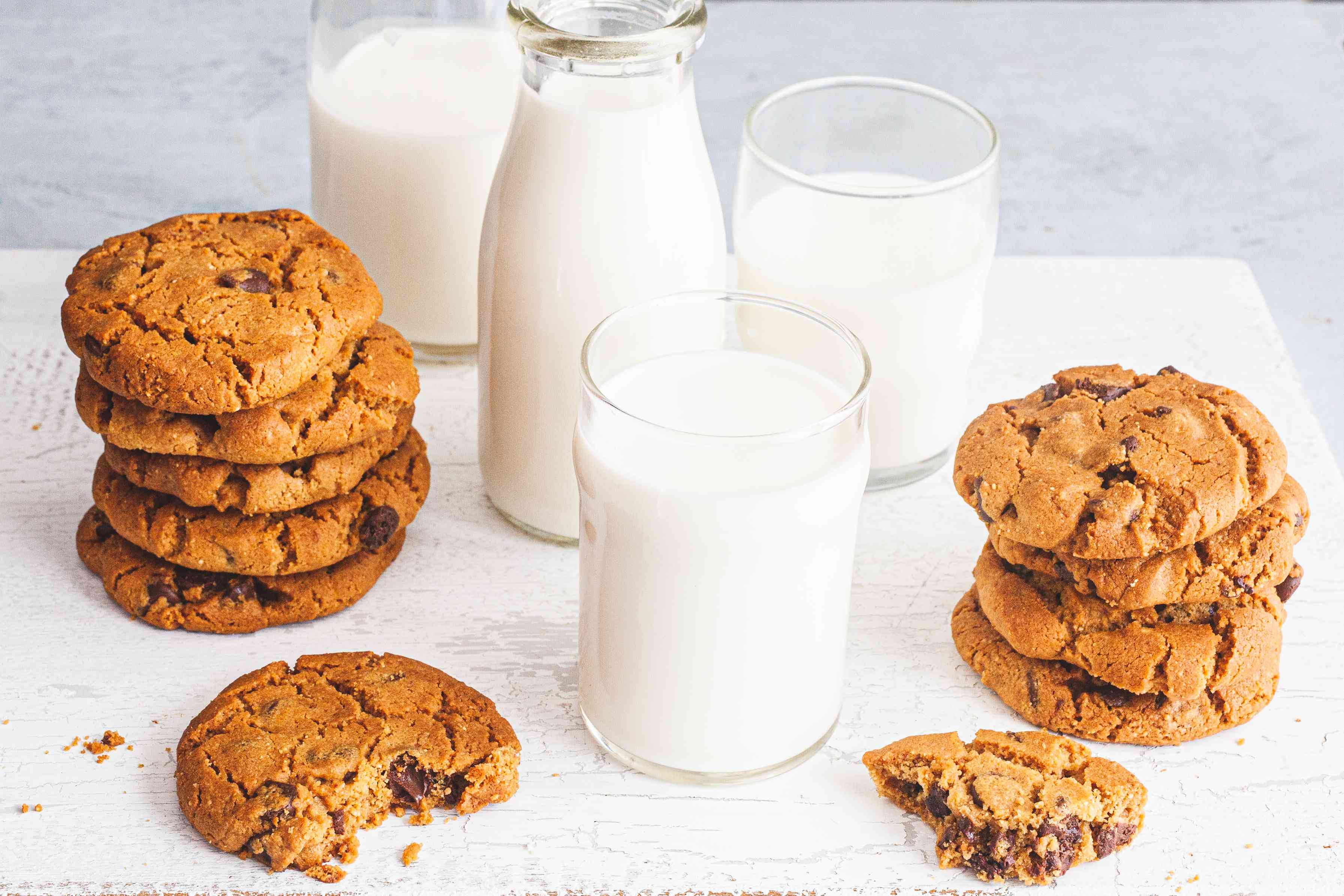 Two stacks of No Mixer Peanut Butter Chocolate Chip Cookies with glasses of milk in-between them.
