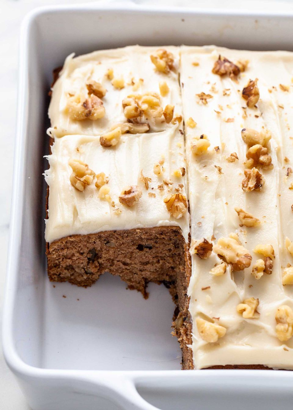 Applesauce spice cake frosted and topped with nuts.