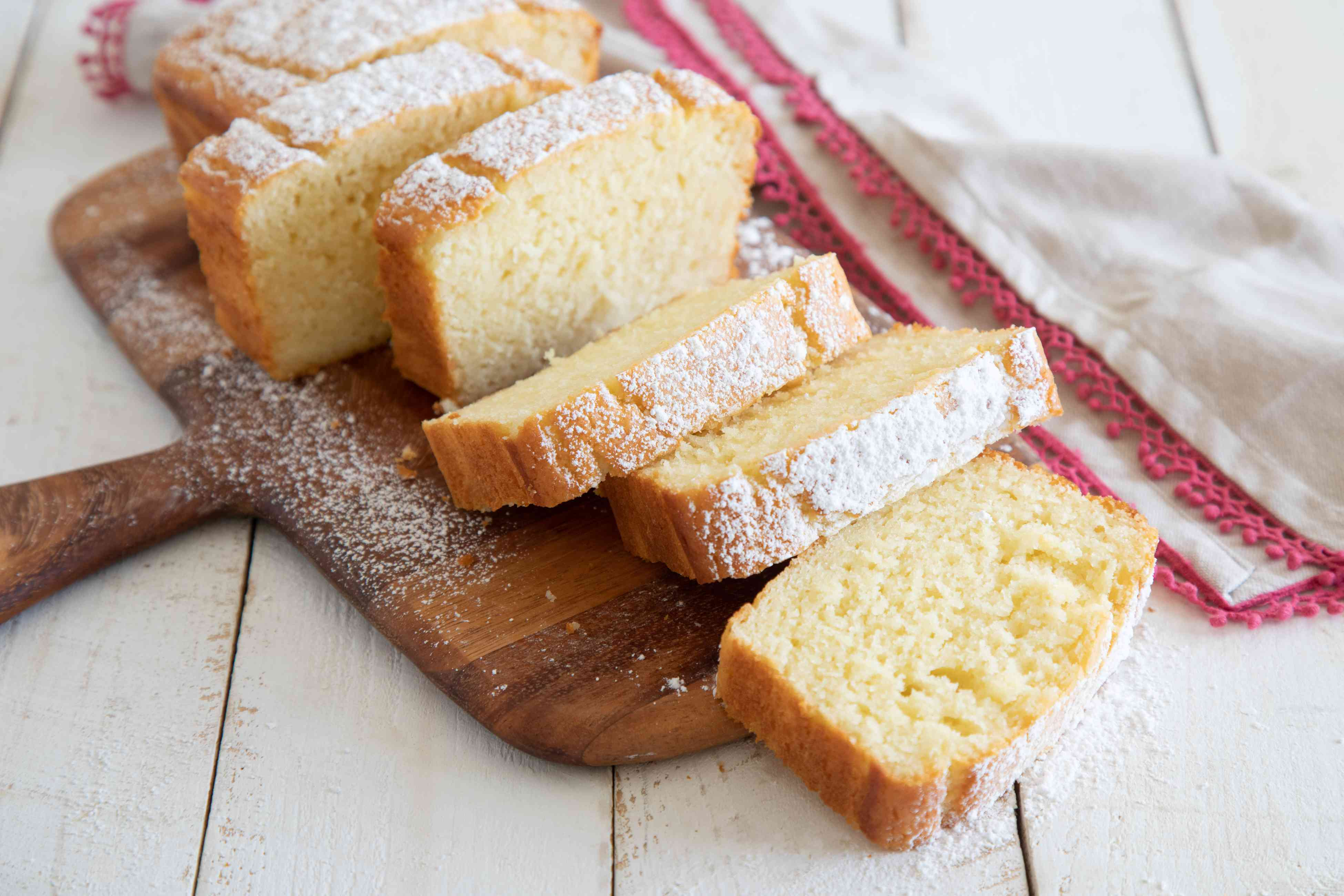 Slices of A slice of Olive Oil Yogurt Cake on a wooden paddle and dusted with powdered sugar.