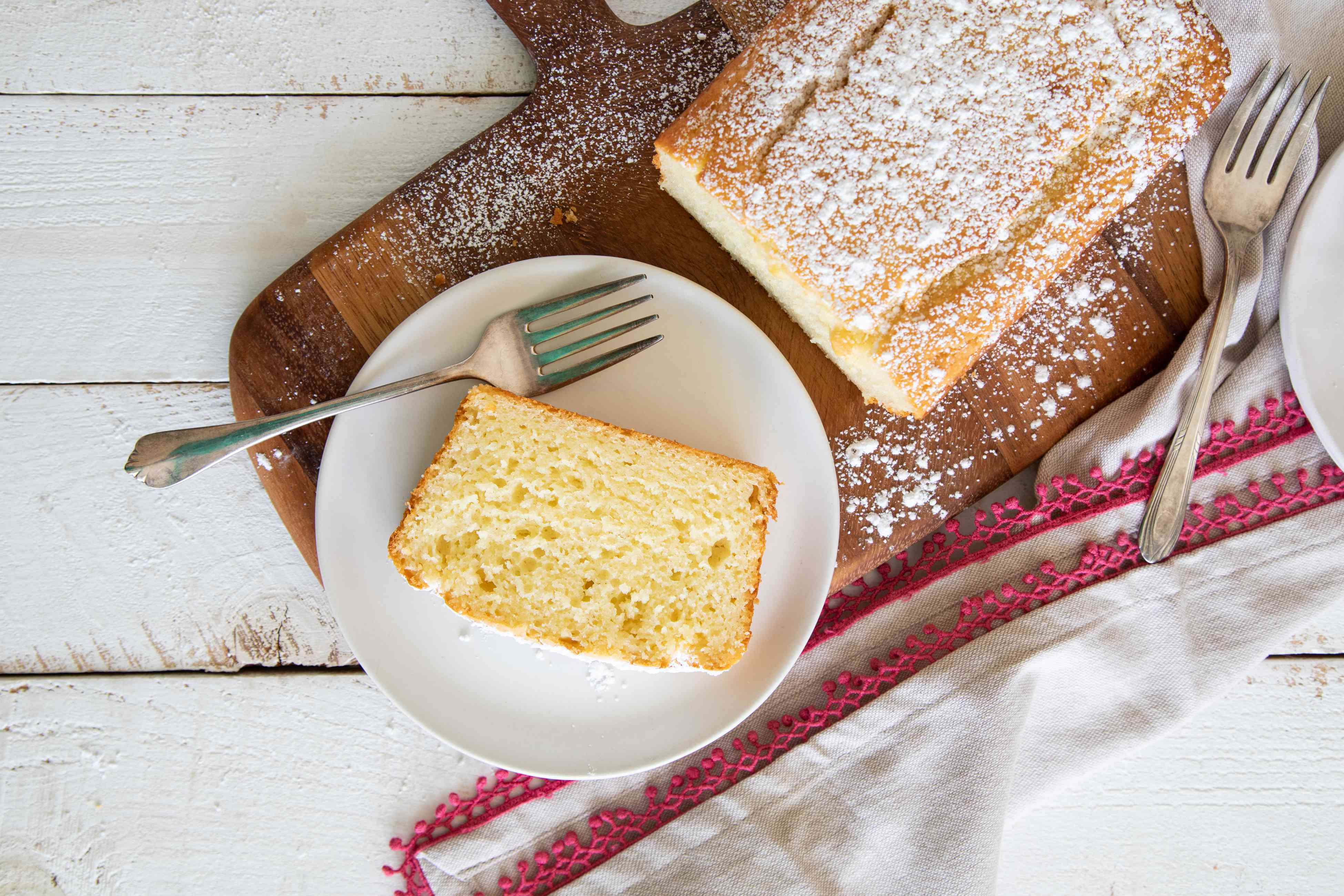 A slice of Olive Oil Yogurt Cake on a plate with the rest of the loaf next to it.