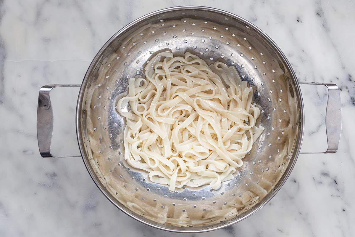 Cooked udon noodles draining in a colander.