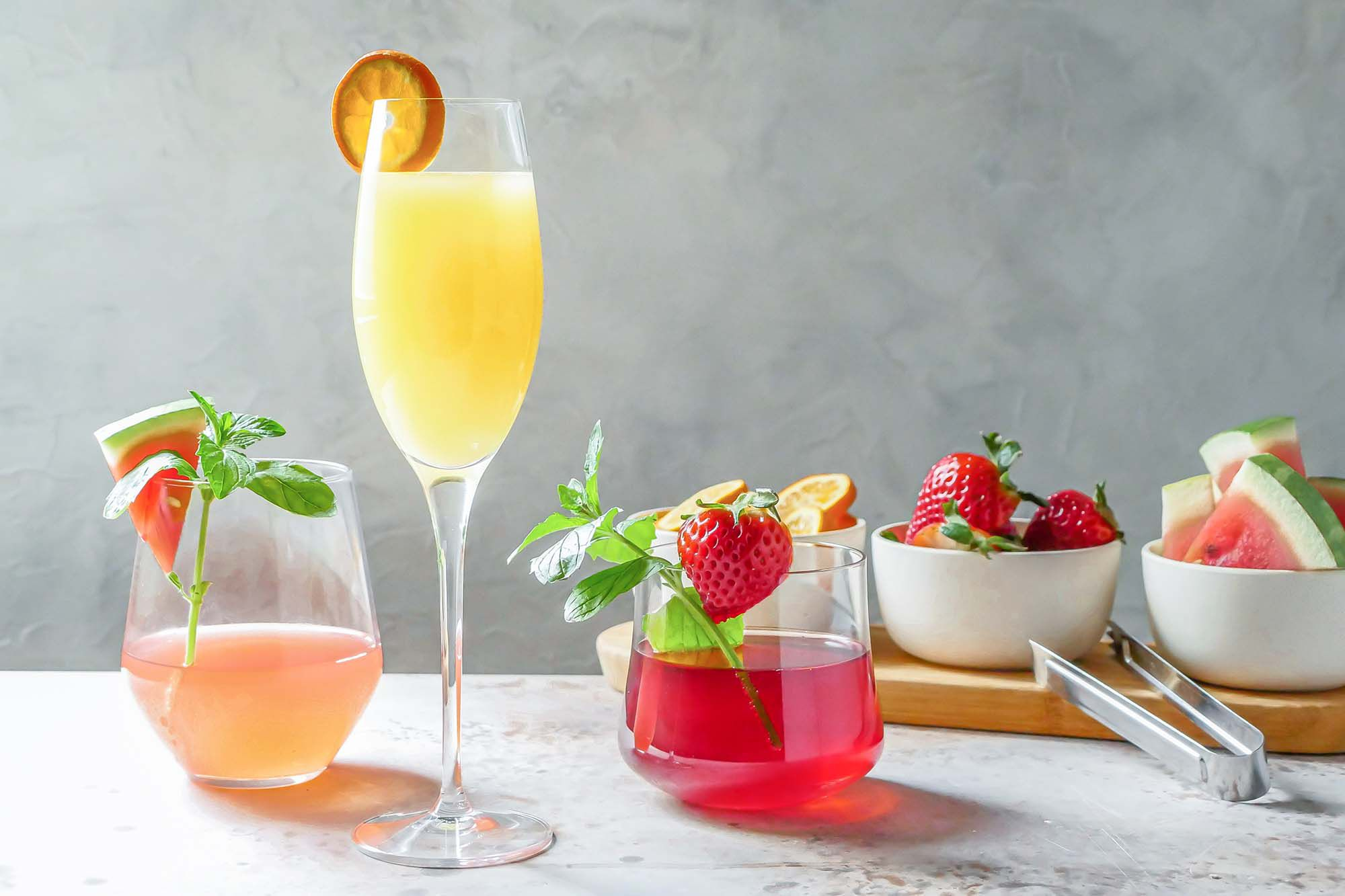 A variety of mimosas on a table and garnished with fruit for a DIY Mimosa Bar.