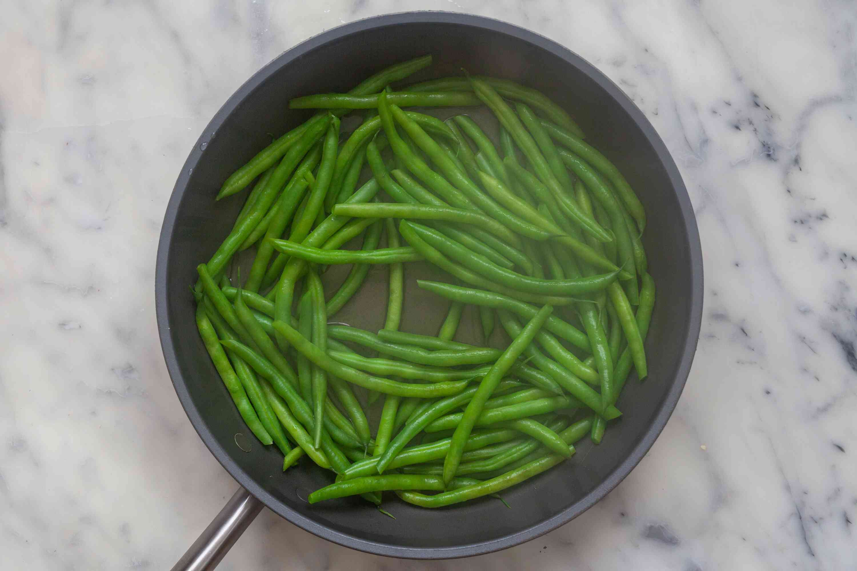 Green beans cooked in a skillet to make Blistered Green Beans with Gochujang.