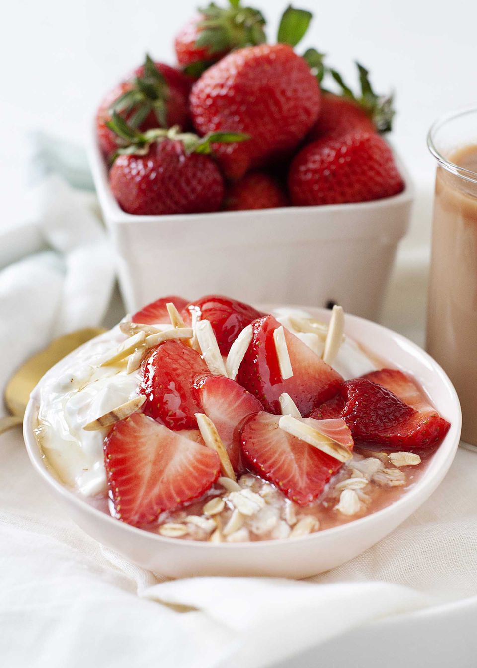 Side view of a tray filled with a creamy coffee, the best overnight oats and a pint of strawberries.