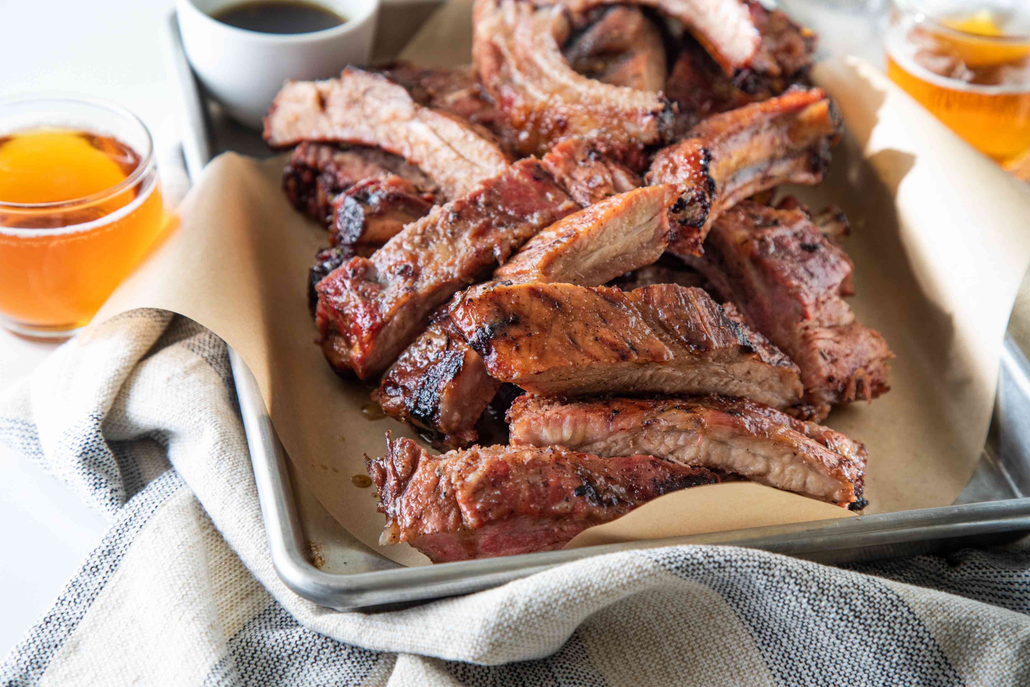 A parchment lined baking sheet with cut ribs from a grilled ribs recipe.