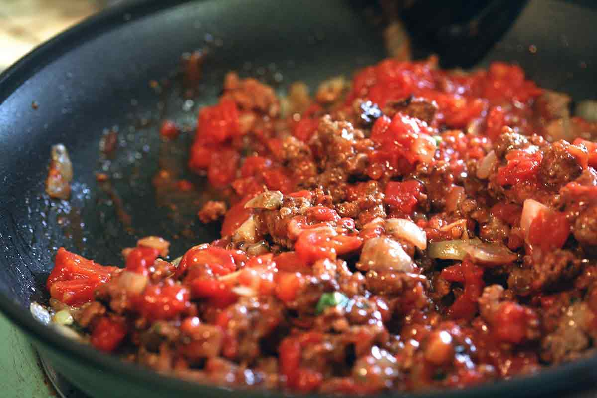 add tomatoes to the ground meat and onions for the penne pasta sauce