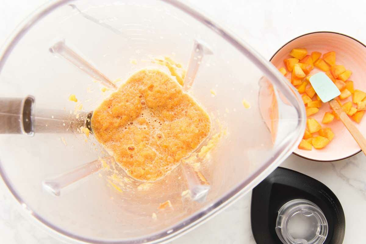 Overhead view of a blender with peach puree inside to make easy peach cobbler ice cream. Chopped peaches are in a bowl to the right.