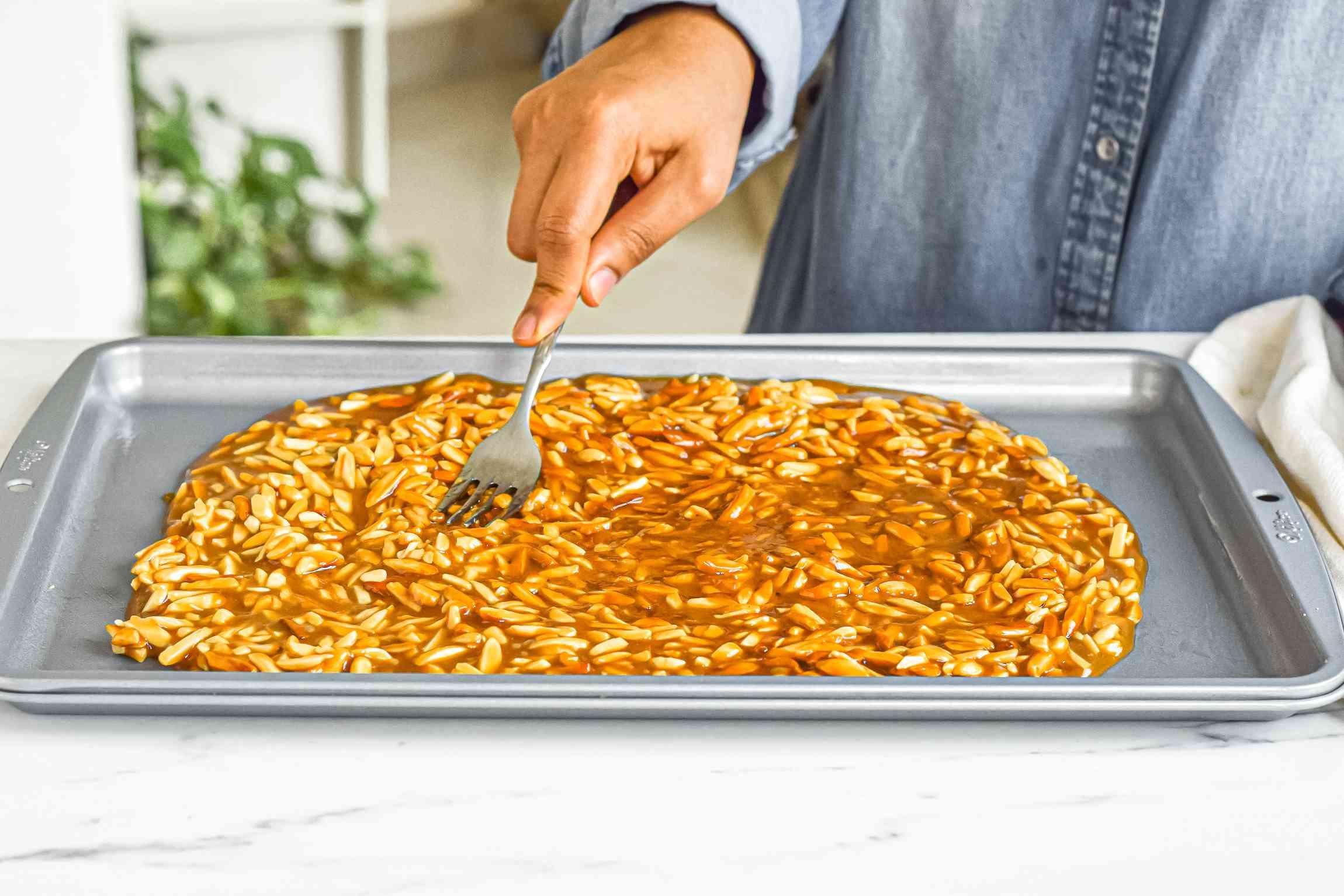 Spreading almond roca on a baking sheet.