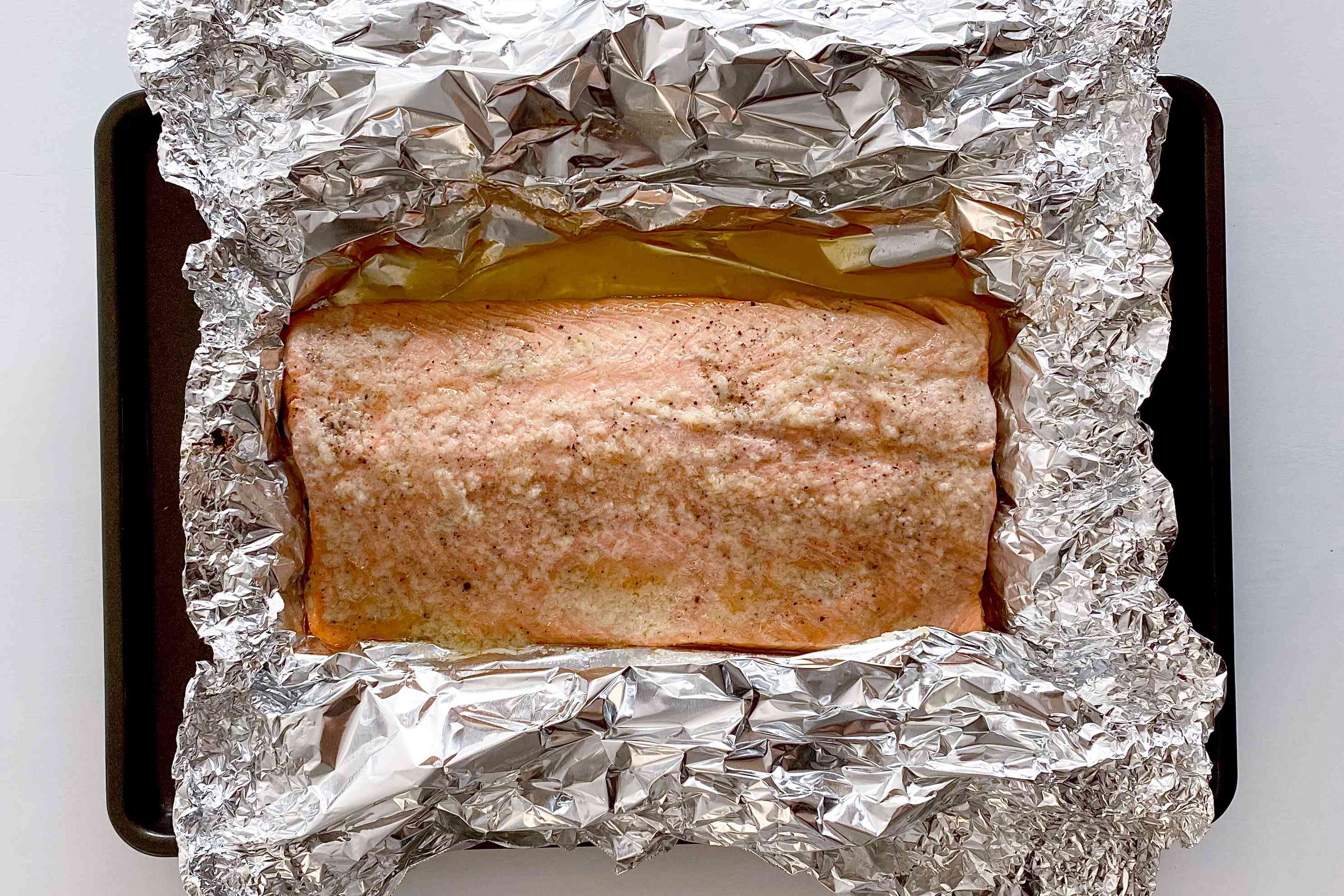 Honey Garlic Butter Roasted Salmon out of the oven and resting in the foil.