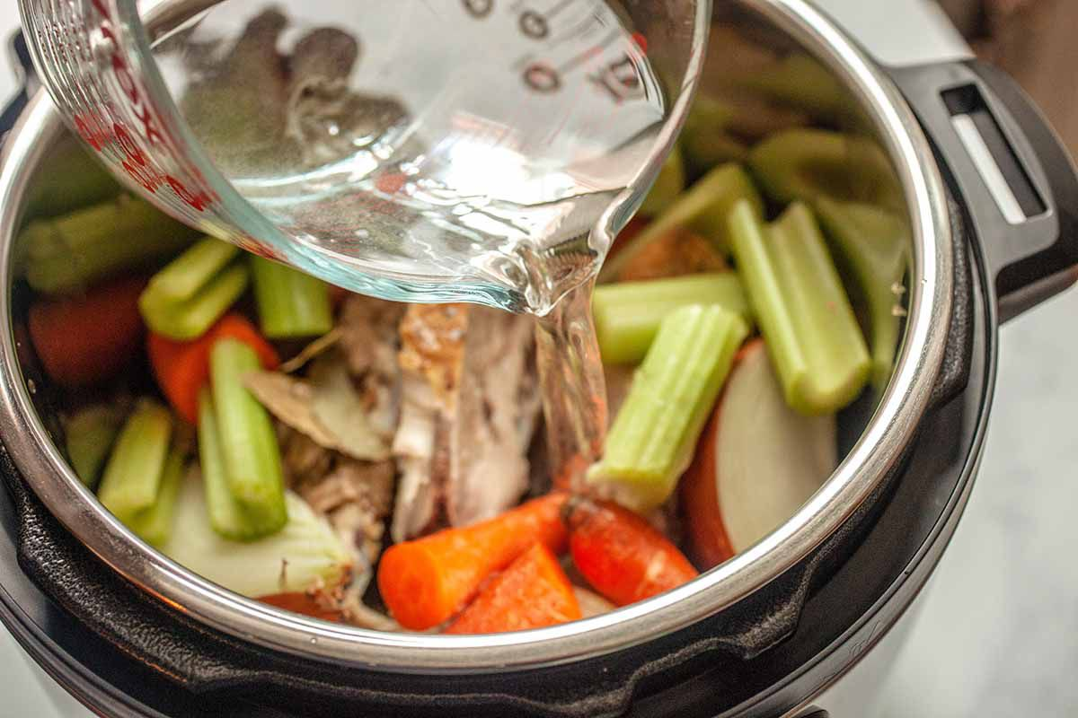 Pressure Cooker Chicken Stock - water being poured over vegetables and chicken bones in an instant pot