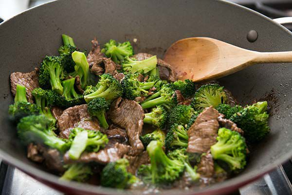 beef and broccoli in wok with wooden spoon