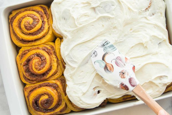 A pan of Homemade Pumpkin Cinnamon Rolls are being frosted.