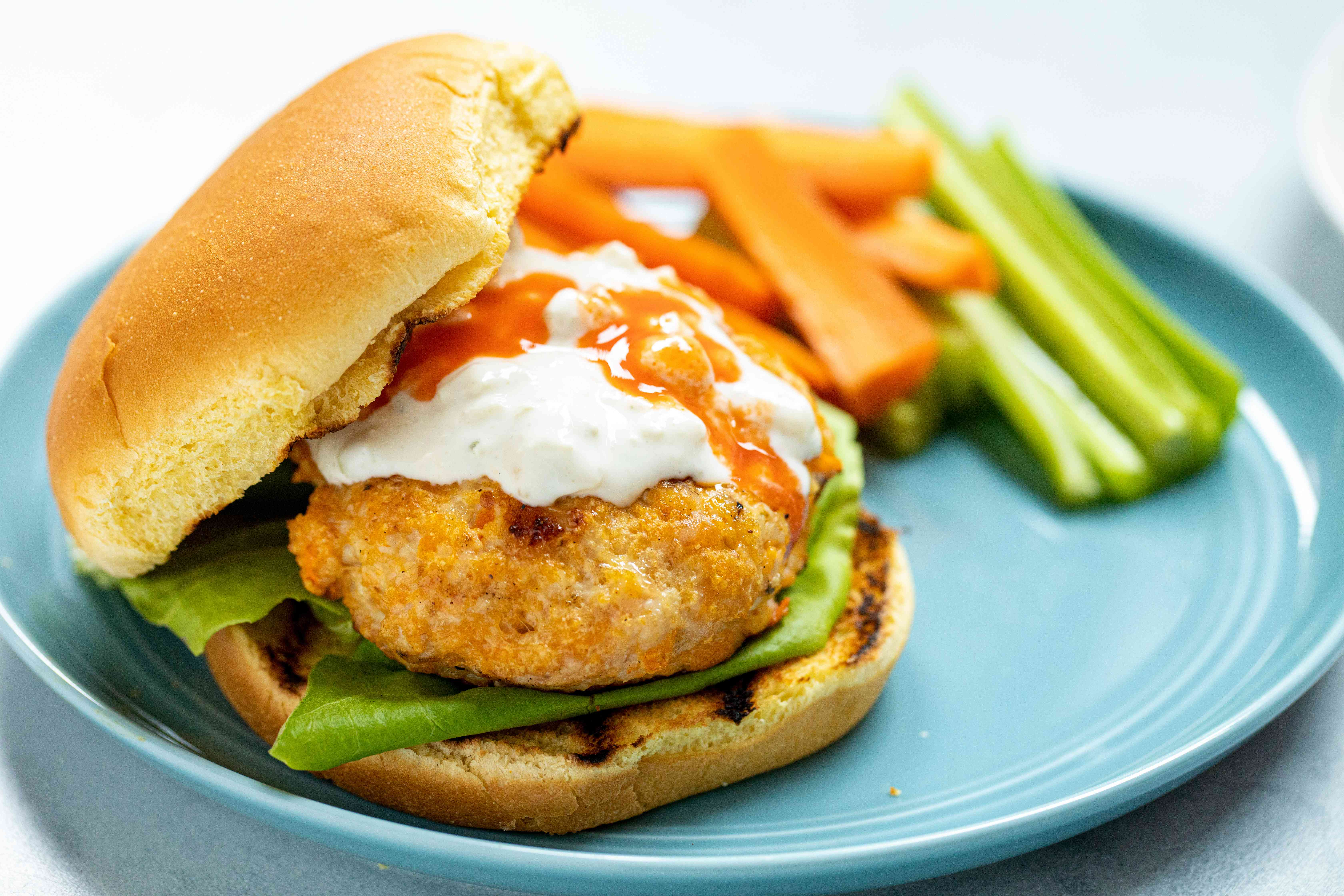 Buffalo chicken burgers with blue cheese sauce on a plate with carrots and celery.