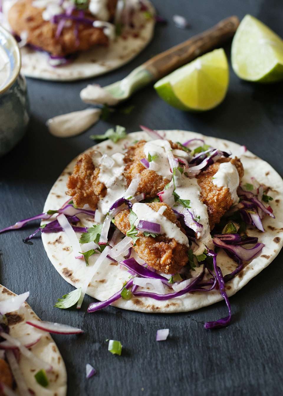 No Alcohol Battered Fish Tacos - fish tacos on grey slate with crema and lime