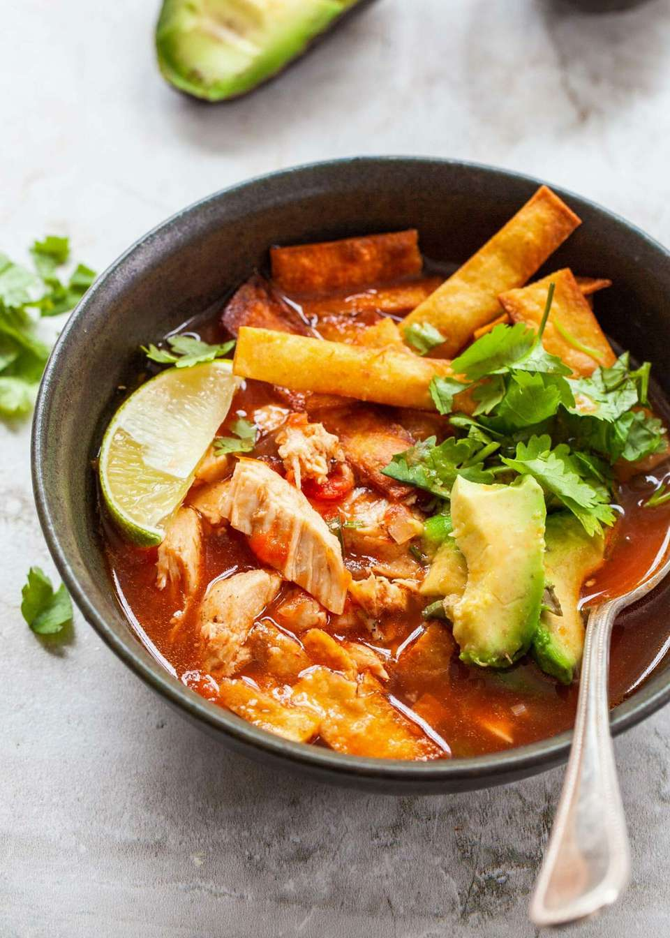 chicken tortilla soup in bowl with spoo