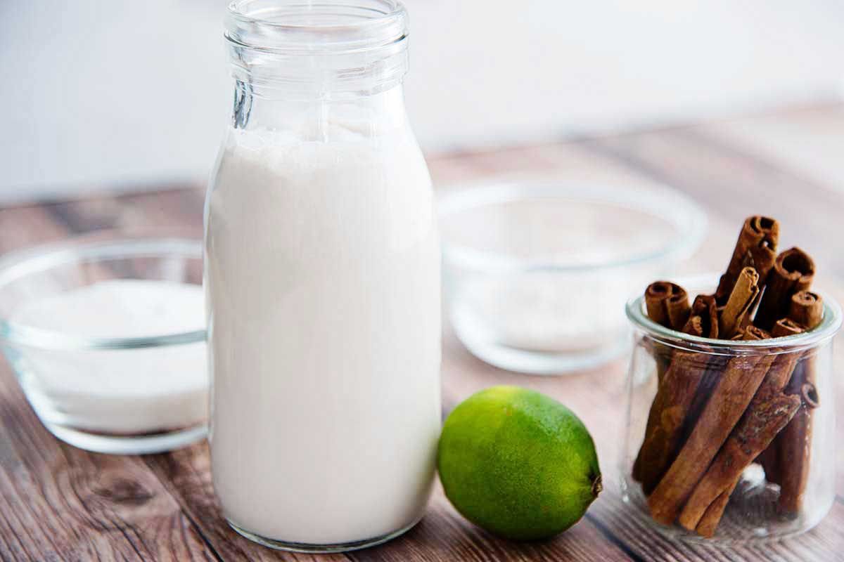 Side view of a glass milk jar with coconut milk insdie. A whole lime and a glass jar of cinnamon sticks are to the right of the milk. Behind the milk are two small glass containters with white ingredients inside.