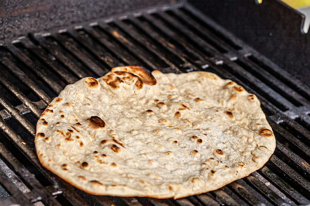 A crust for the best grilled pizza on a grill and getting golden and bubbly.