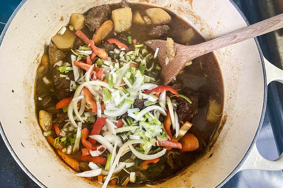 Sliced vegetables added to the pot for Jamaican Stewed Beef.