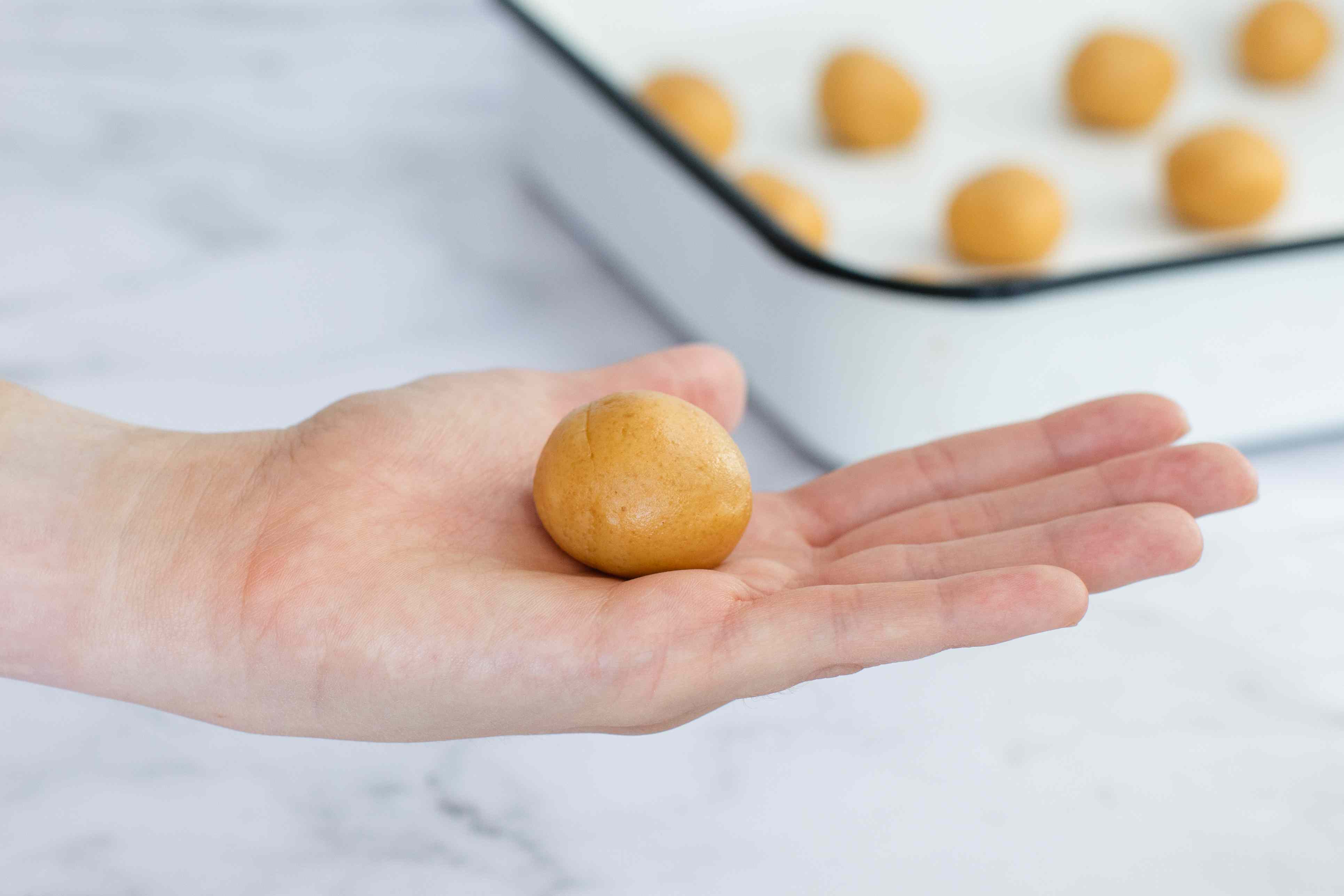 Rolling Peanut Butter Cookies in a ball.