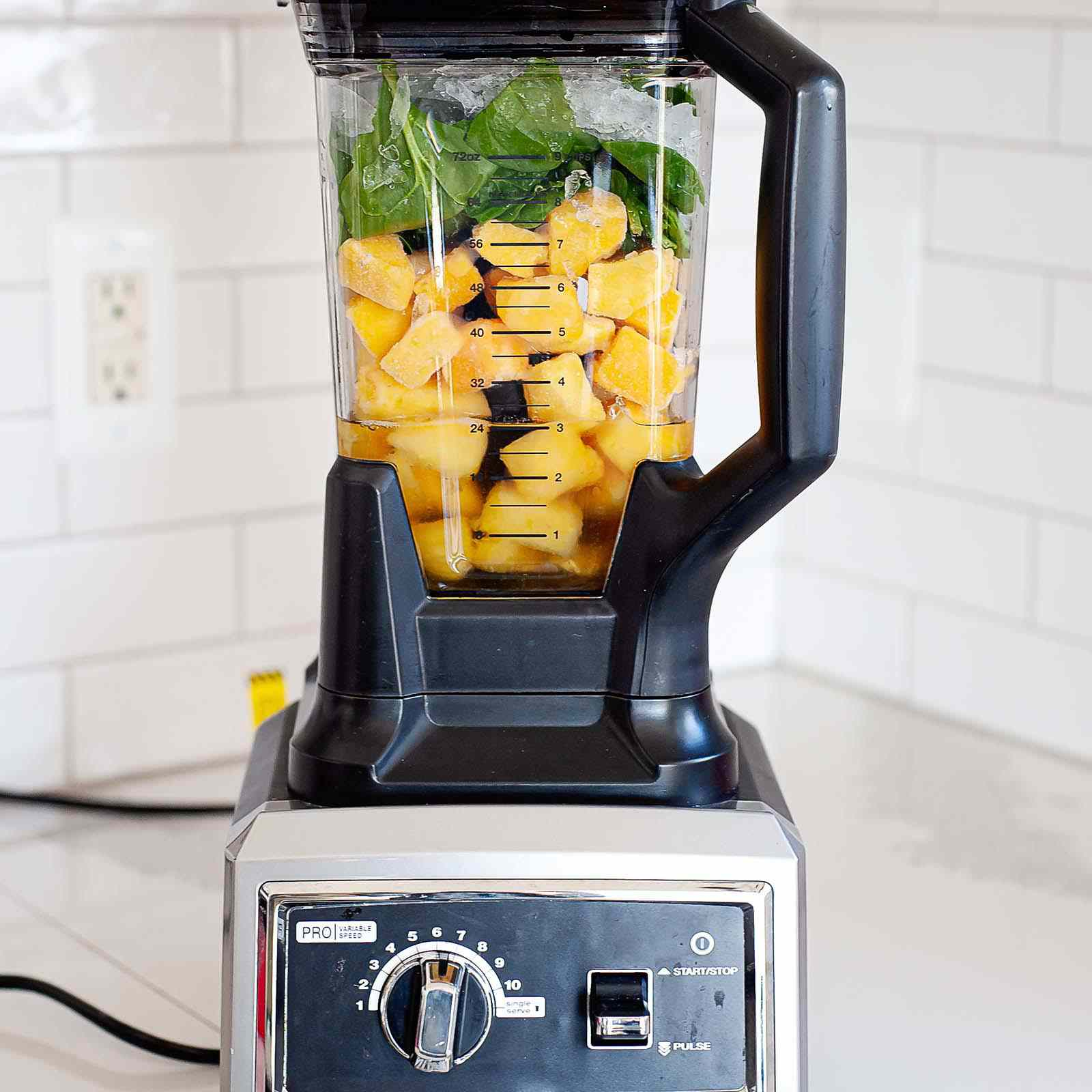 View of a high speed blender with pineapple and spinach inside. The blender sits on a white counter with subway tiled backsplash behind it.