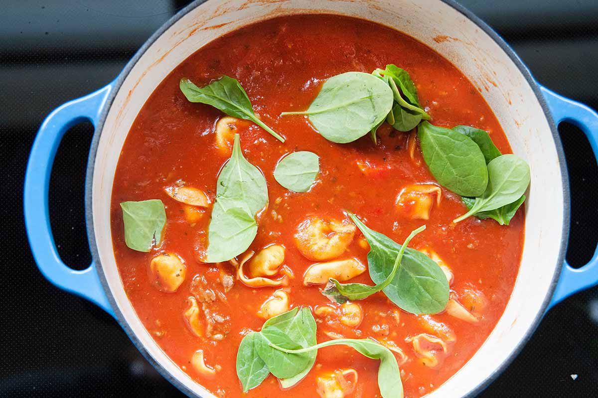 Tomato Spinach Tortellini Soup - shot of tortellini soup in pot with spinach
