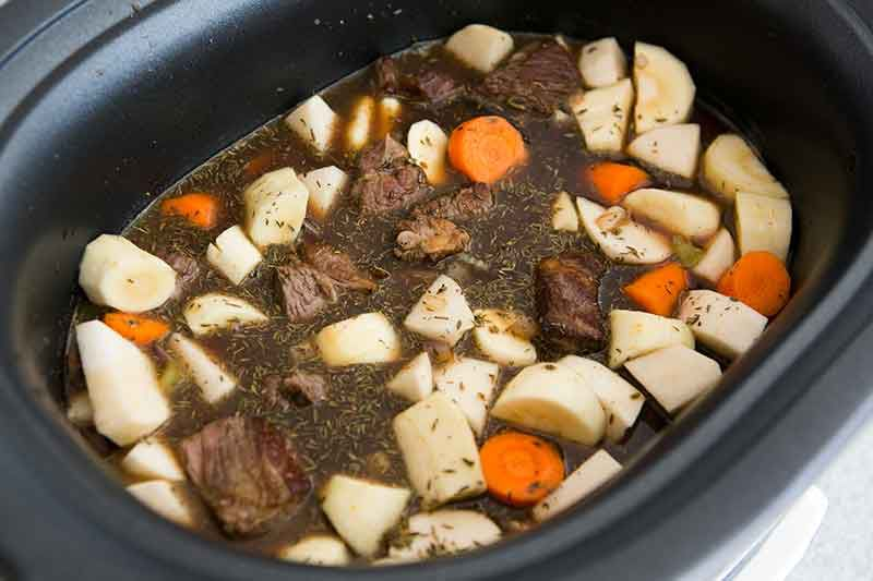 Crock pot Guinness beef stew being prepared and made ready to cook in slow cooker