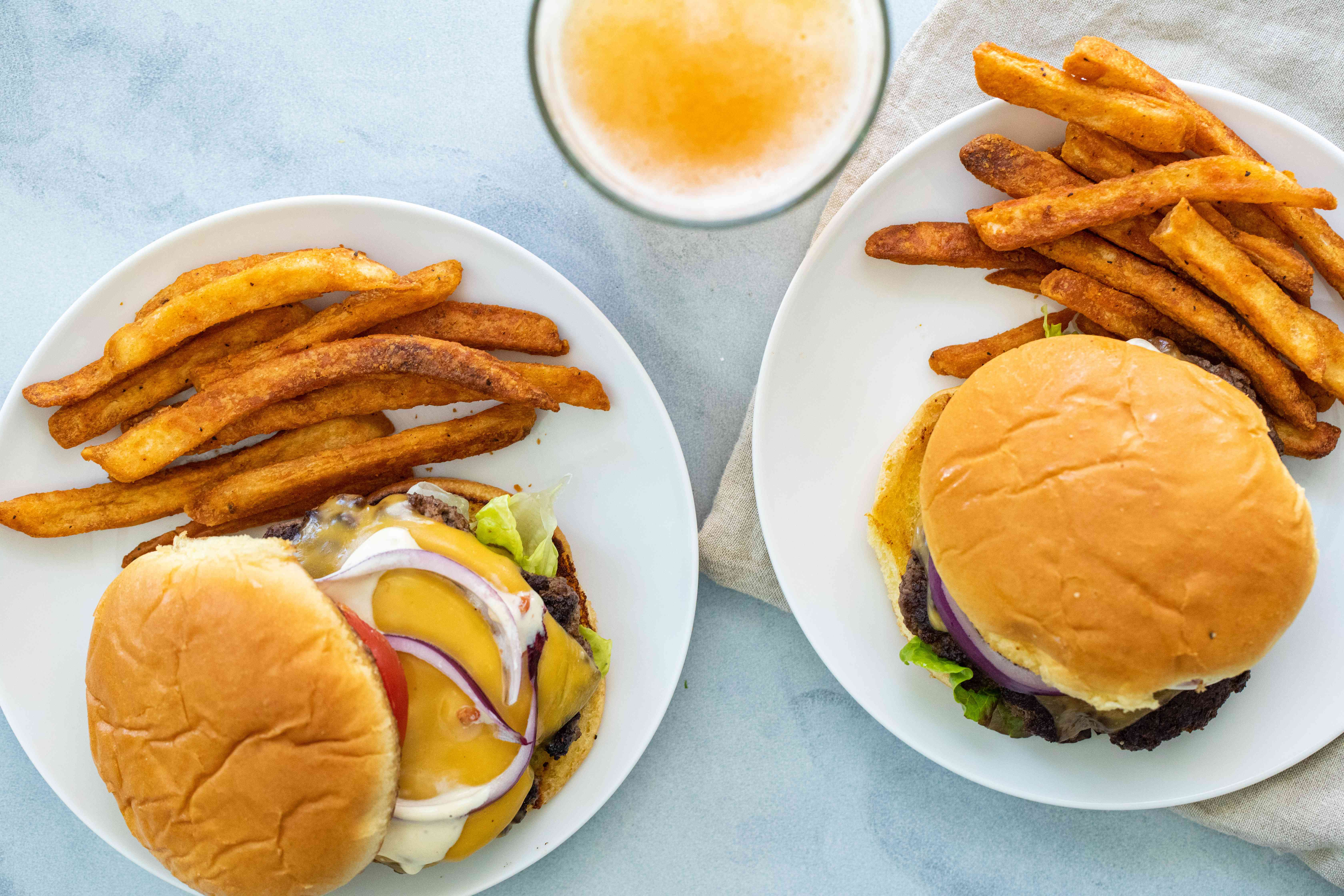 Overhead view of two plates with homemade smashburgers and fries.