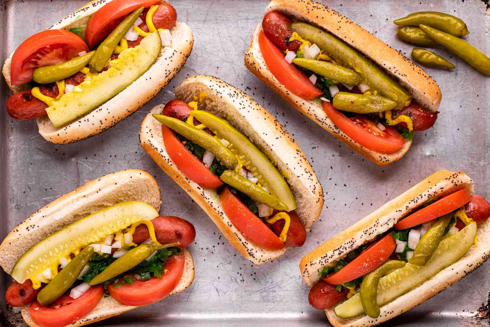 Overhead view of a sheet pan with Chicago-style hot dogs on it.