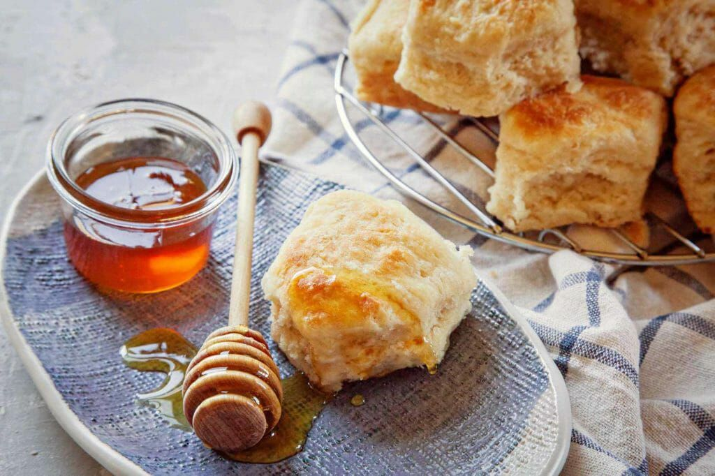 Angel biscuits served with honey on a blue plate