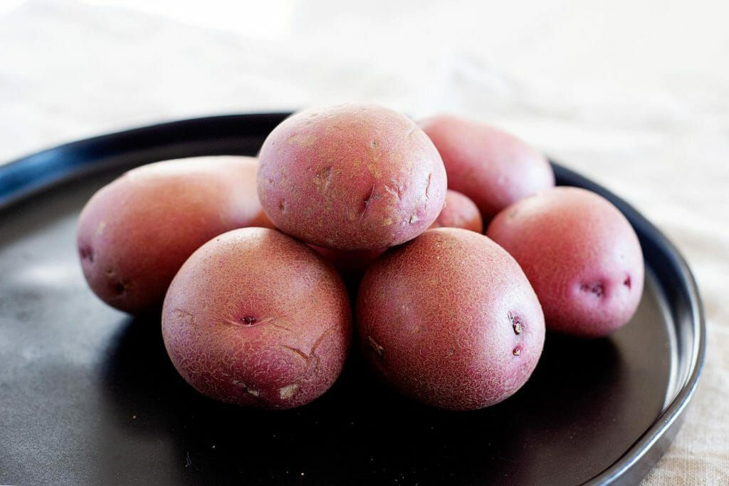 Side view of a stack of red potatoes on a black tray.