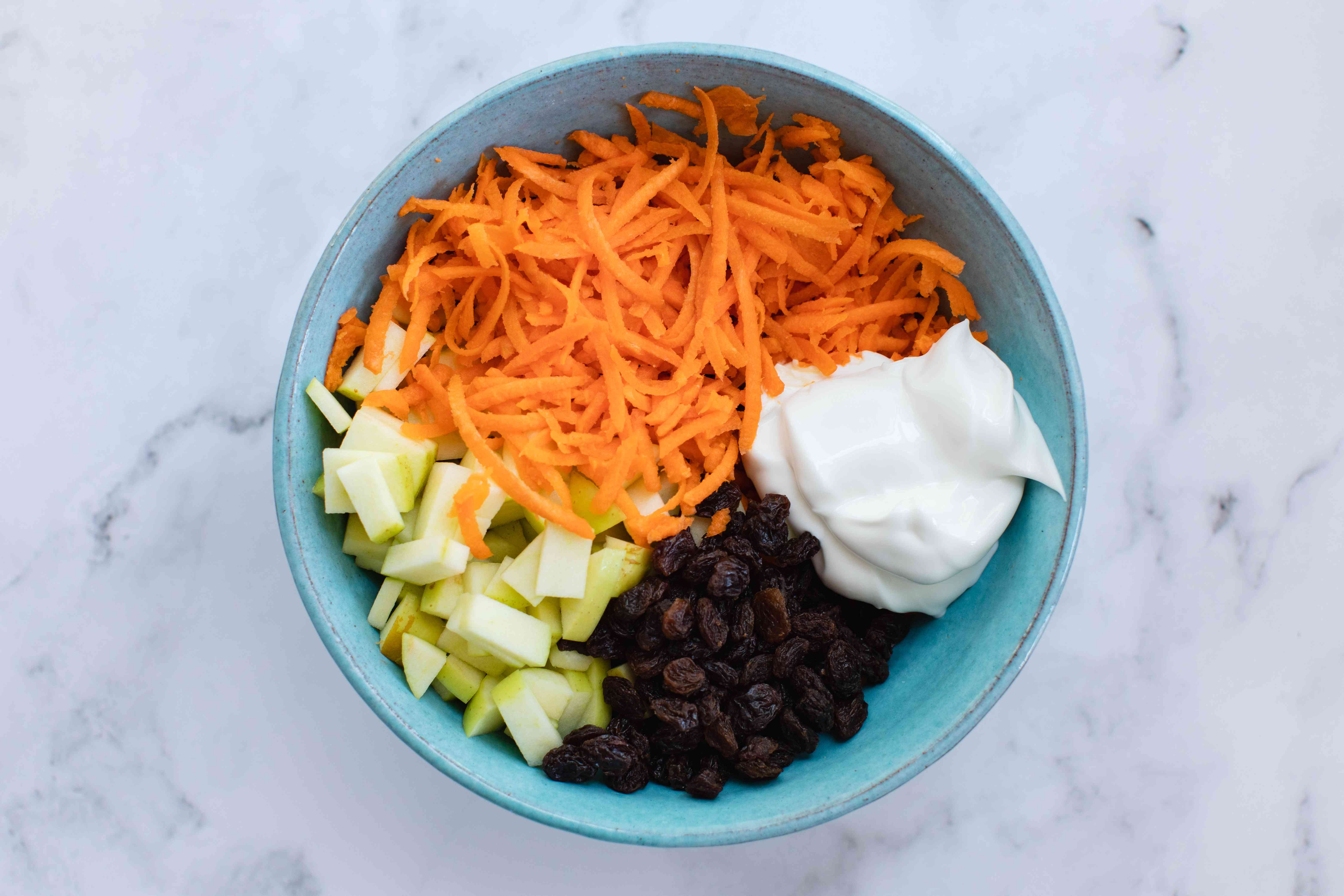 Ingredients to make a Classic Carrot Salad in a bowl.
