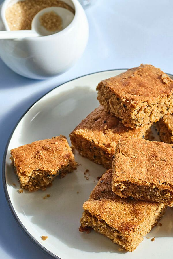 Stack of tahini blondies from the cookbook Sababa on a white plate with a light blue background and a bowl of sugar and coffee nearby.