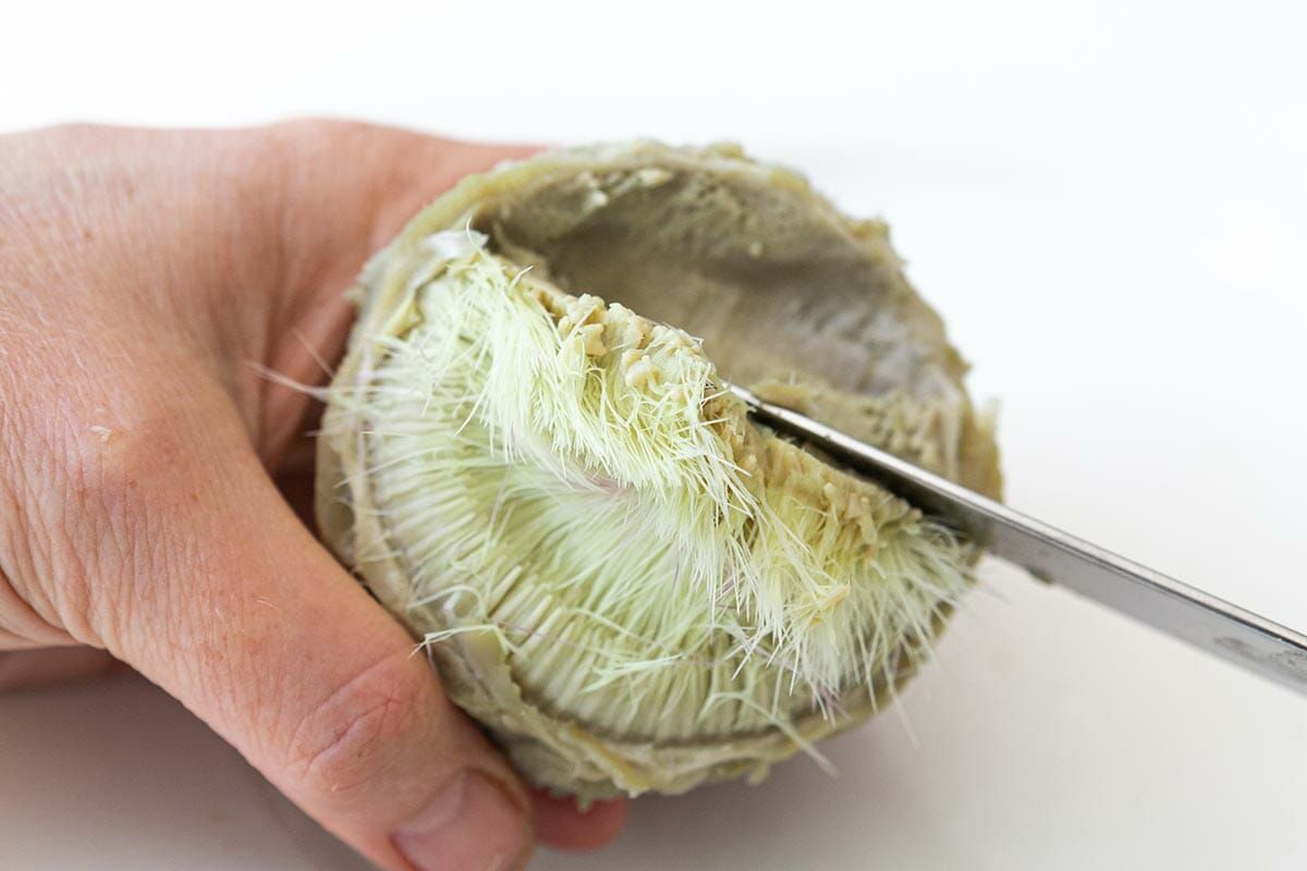 Scrape out and discard the choke from the very inside of the artichoke