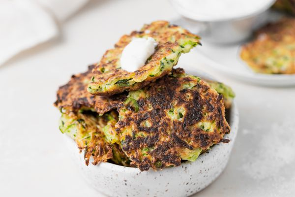 A bowl of zucchini fritters set on a white background.