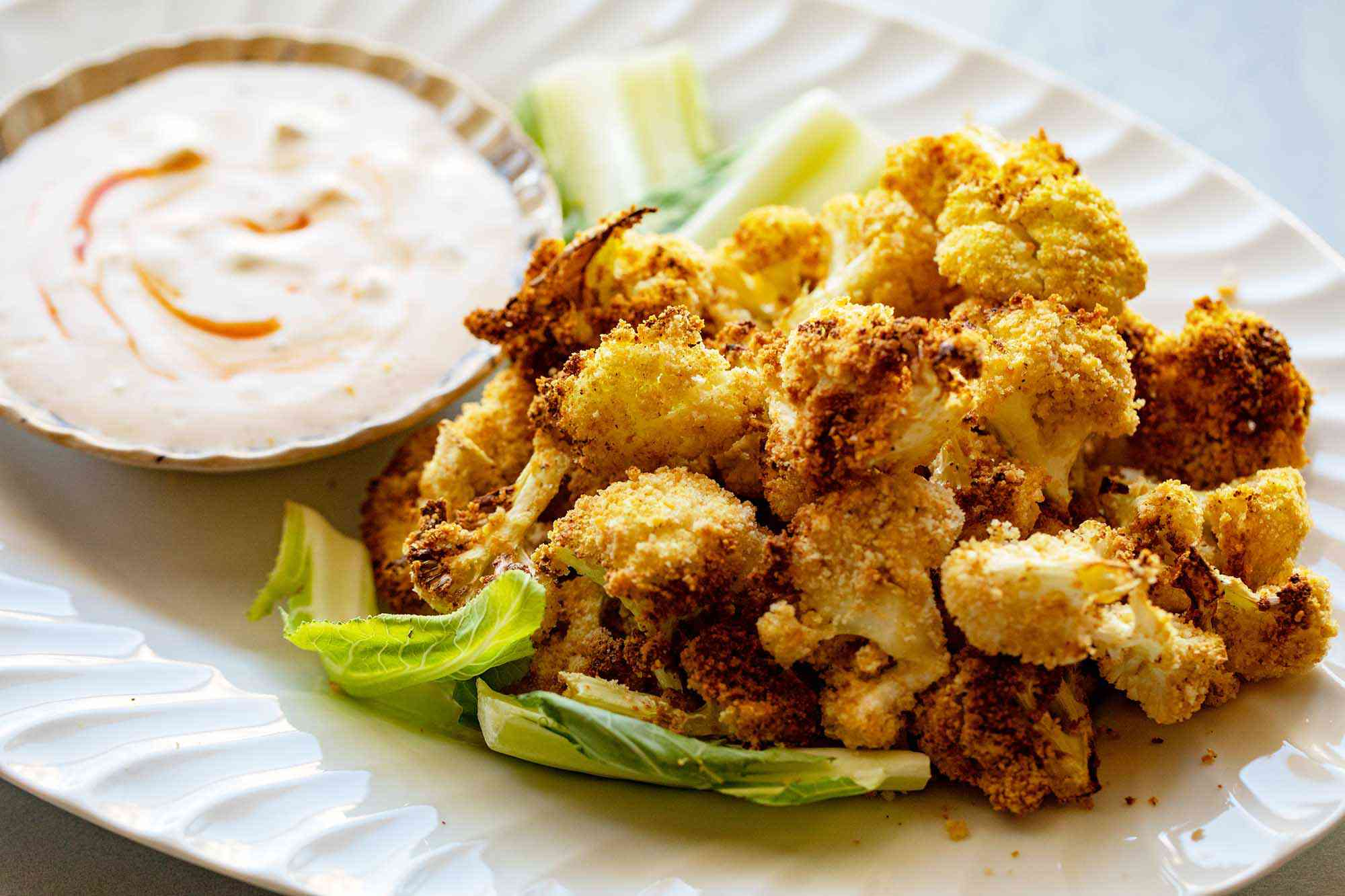 Platter of golden air fried crispy cauliflower heaped on the right of the platter. A small bowl of creamy dip swirled with hot sauce is placed next to the cauliflower on the platter. The cauliflower is resting on a few leaves of lettuce.