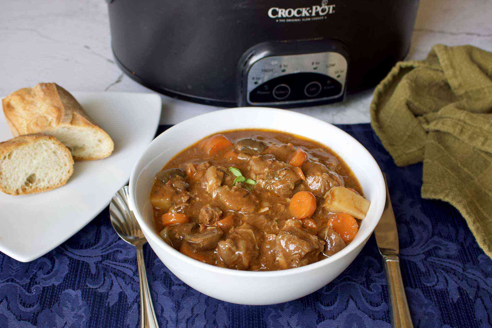 Slow Cooker Beef Burgundy (Boeuf Bourguignon) in a bowl set in front of a crock pot. Silverware, bread, a place mat and kitchen towel are surrounding the bowl.