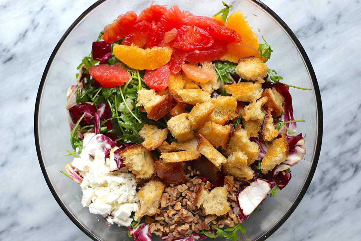 An overhead view of the inside of a large glass bowl. Elements of the bitter green and citrus salad are inside. Homemade croutons are in the middle of the bowl and sit on top of the arugula and radicchio. Feta is in the lower left and supremed oranges and grapefruit are above the croutons.