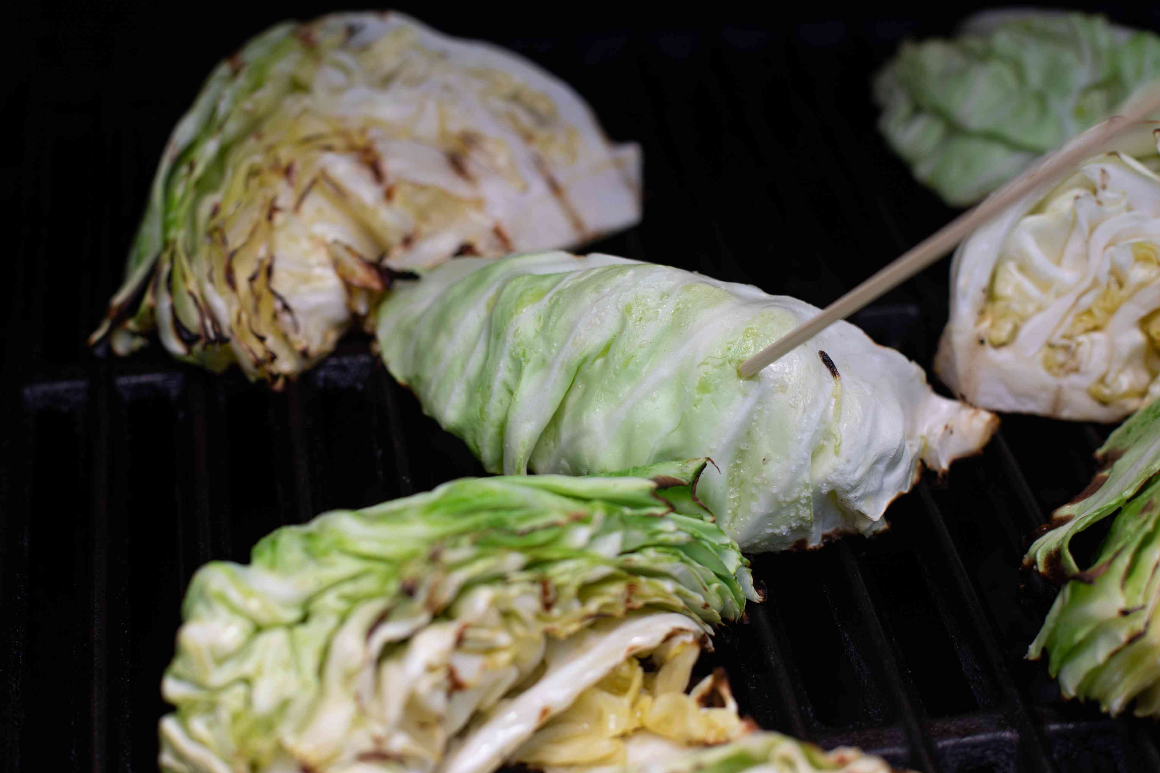 Checking for doneness for grilled cabbage with peanut satay sauce on the grill.