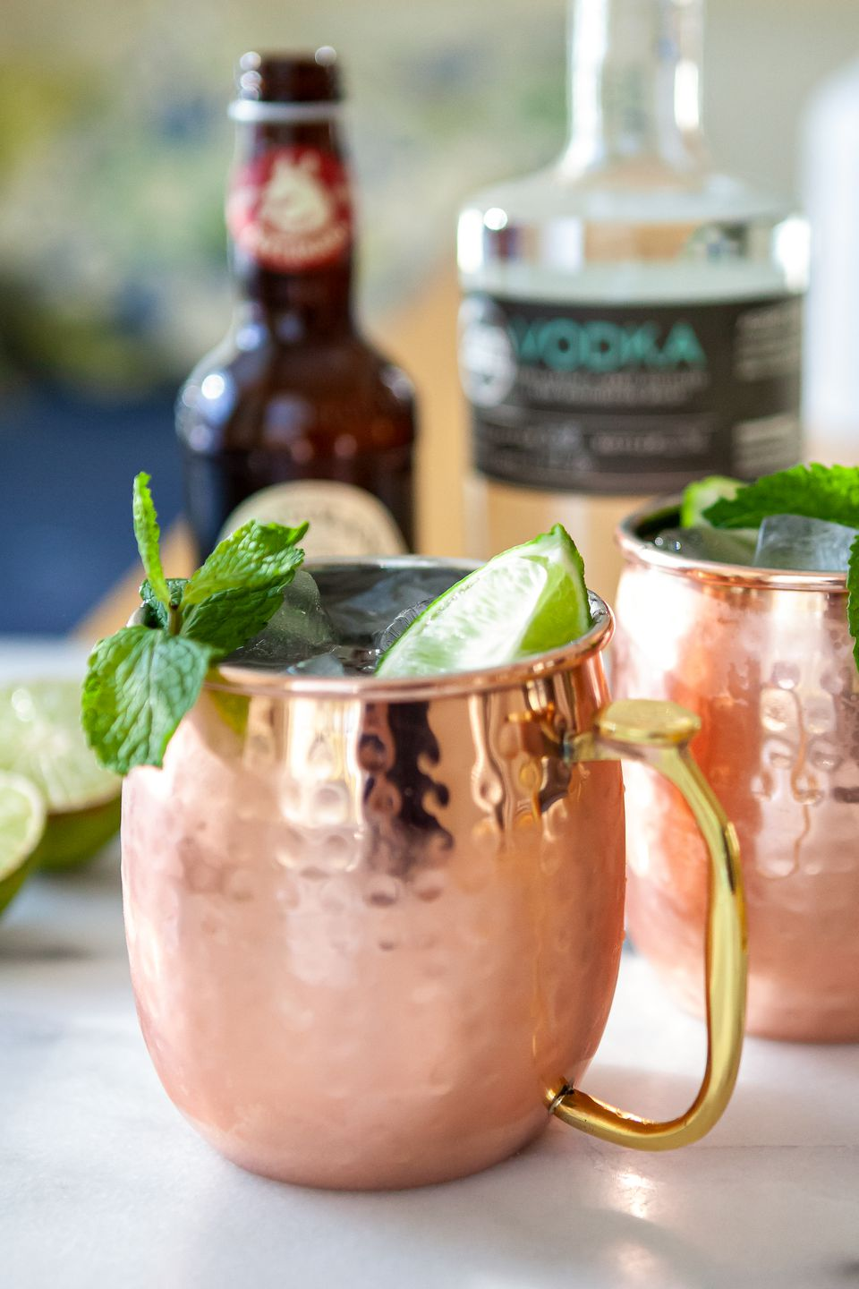 A Moscow Mule Cocktail garnished with mint with bottles set behind the cups.