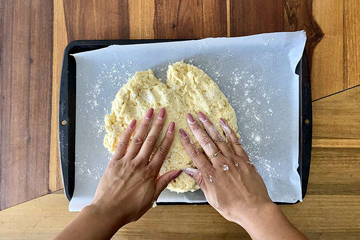 Hands pressing dough into a parchment lined baking sheet to show how to make gluten free cinnamon rolls.