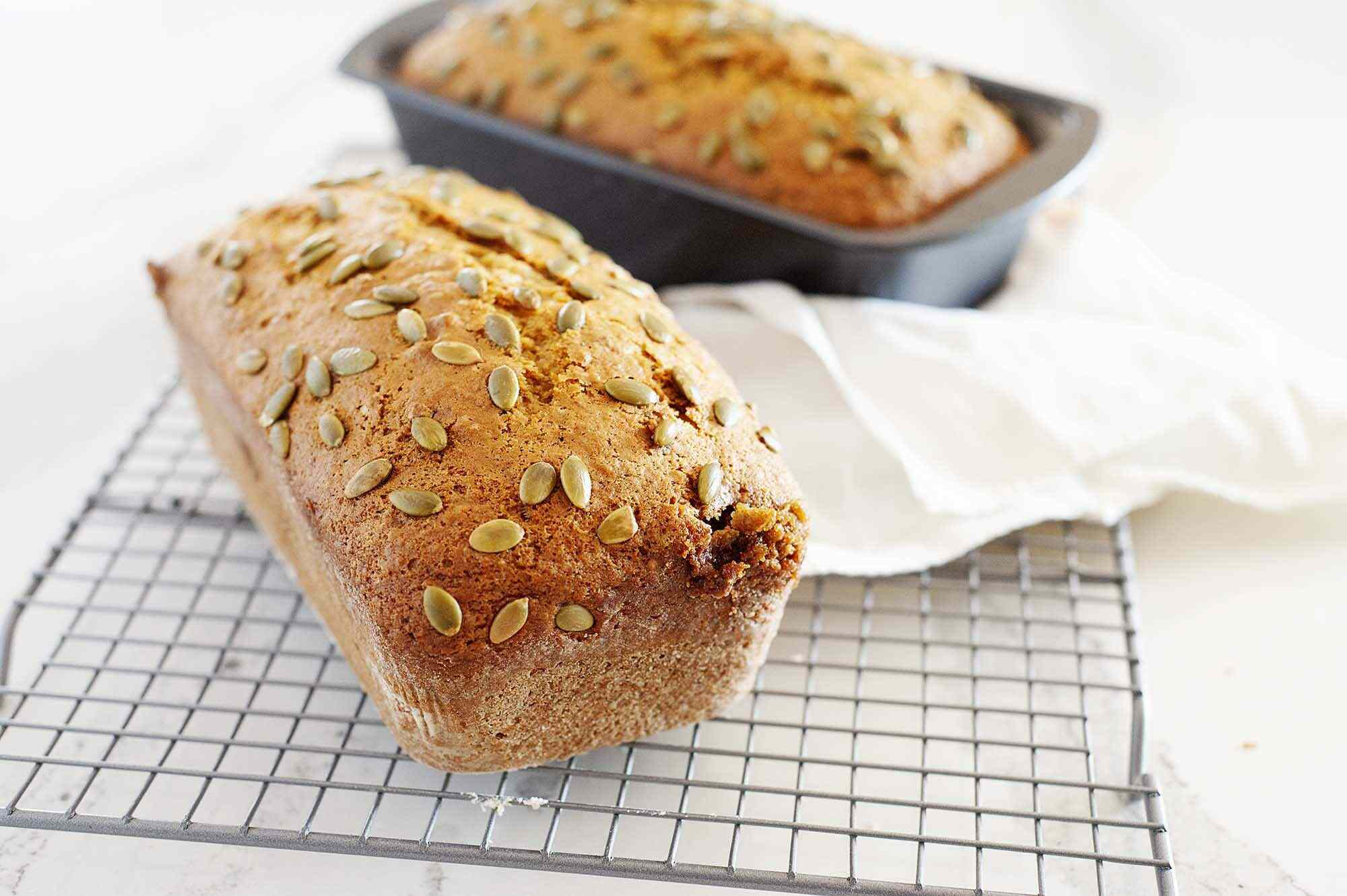 A loaf of Moist Pumpkin Bread cooling on a rack with a second loaf in the pan behind it.