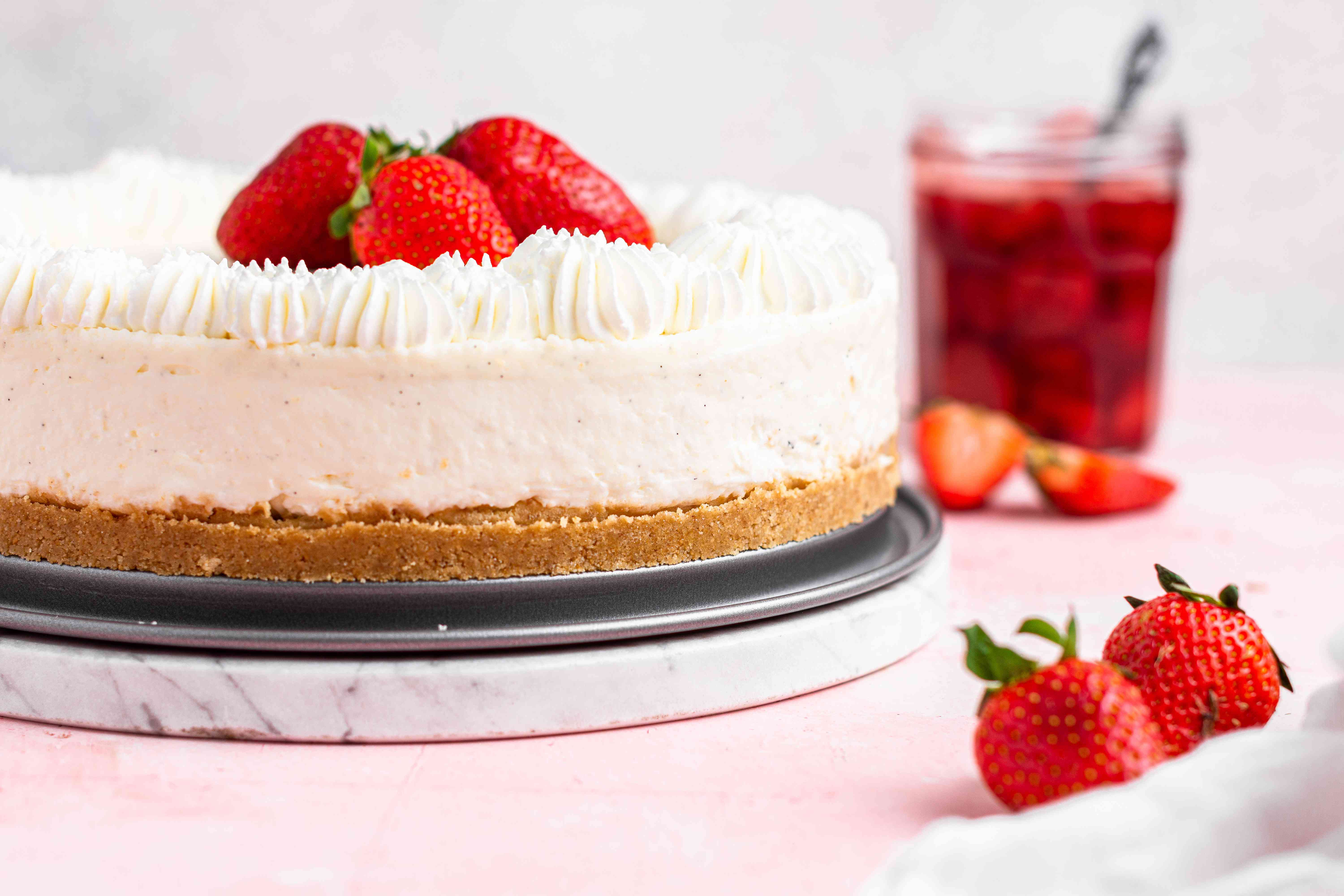 A whole easy no bake cheesecake topped with strawberries on a pink background.