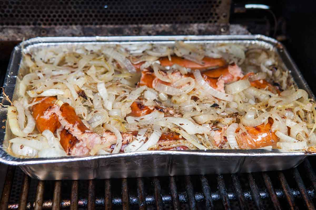 Polish sausage on the grill with sauerkraut and onion