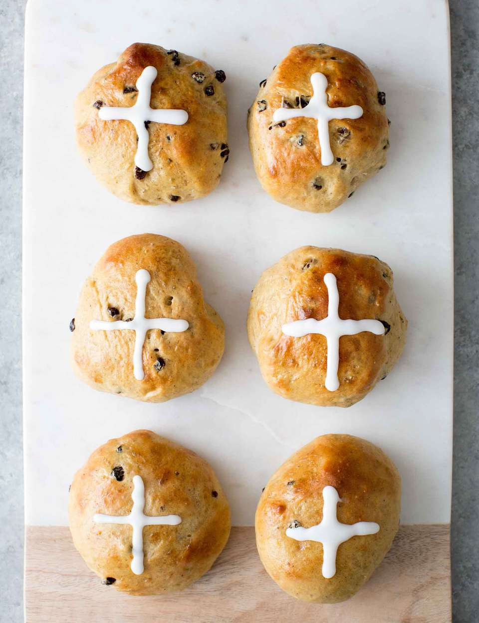Easy Hot Cross Buns with sugar crosses on top on a board for serving