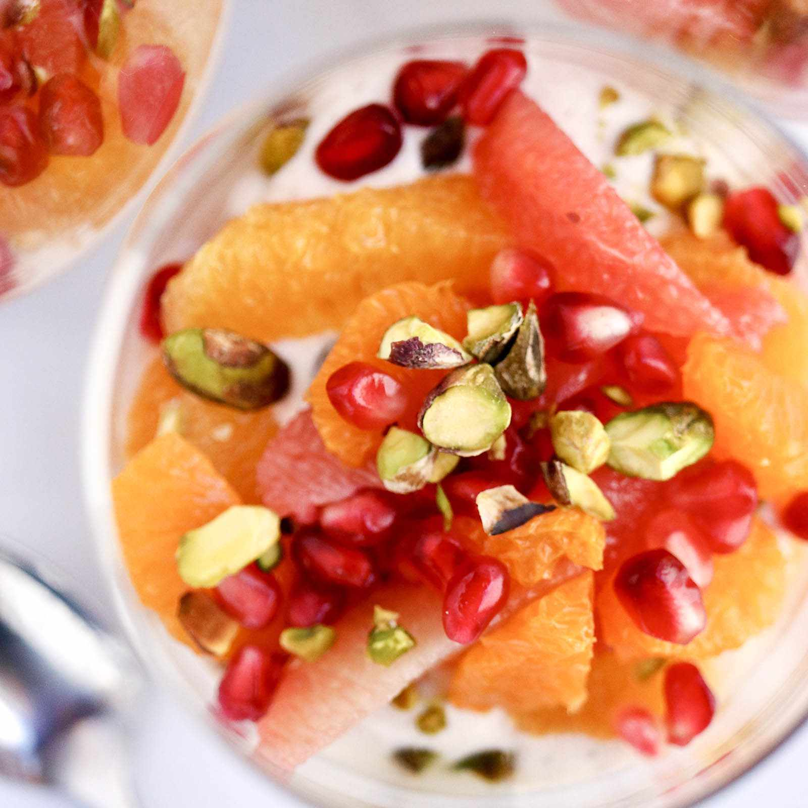 Top down shot of a glass of citrus fruit topped with seeds and nuts against a white surface.