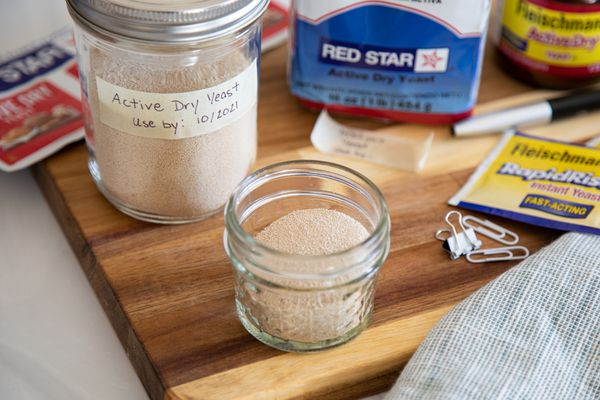 A wooden cutting board with a variety of yeast in their packaging and in mason jars to show how to store yeast.