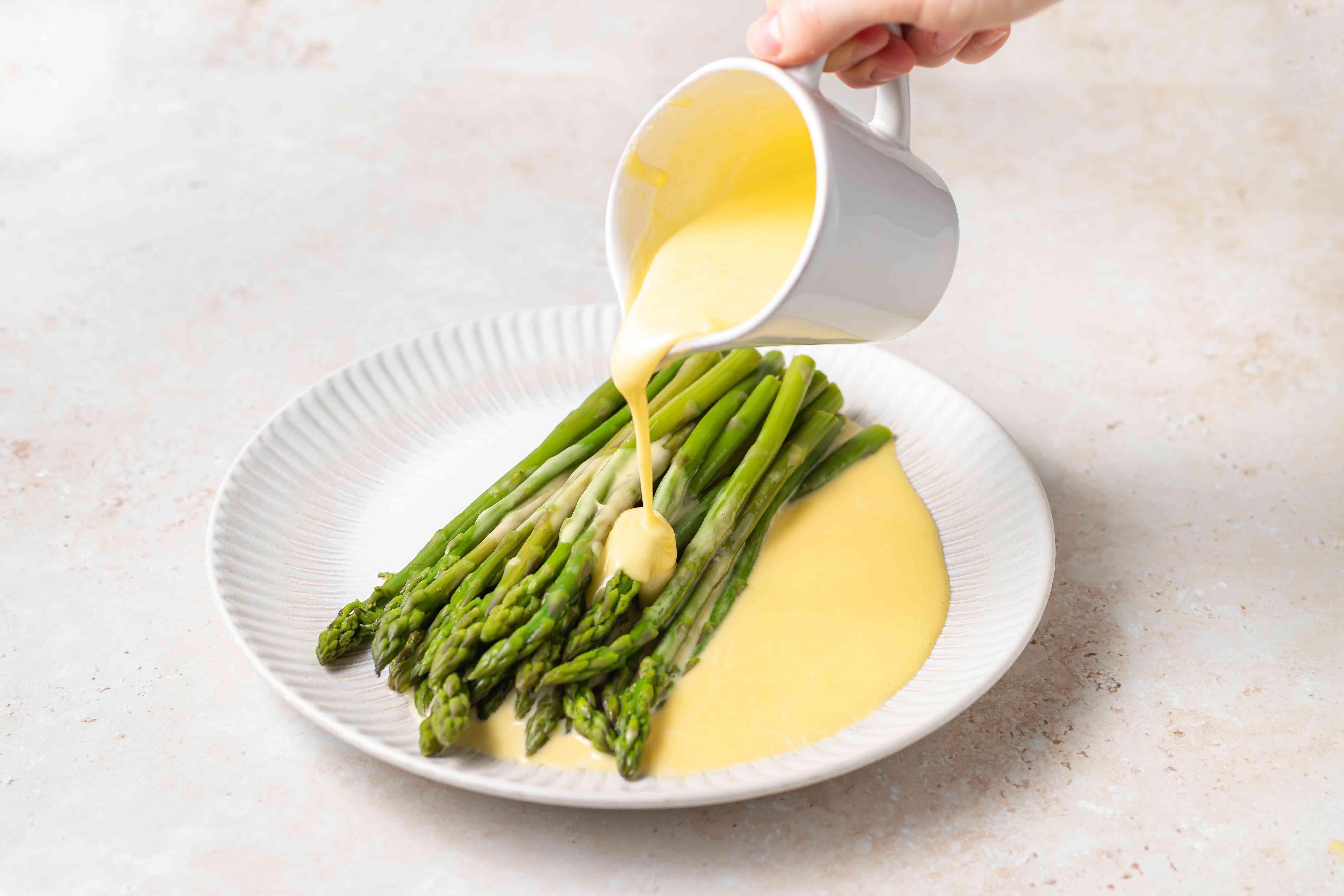 Blender Hollandaise Sauce poured over asparagus.