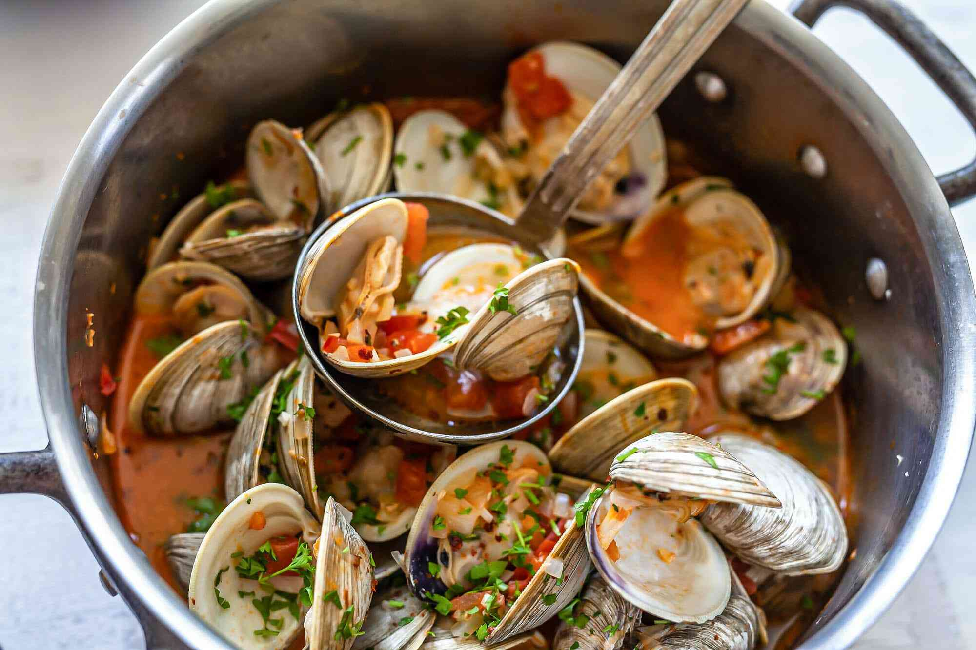 Overhead view of steamed clams with chorizo in a large stockpot. A ladle is resting on top and is full of clams.